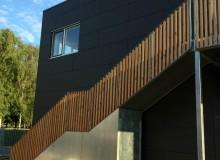 Modulerne har facader beklædt med sorte fibercement-plader og galvaniserede trapper med douglasgran som afskærmning.
