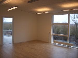 Den indvendige del er udført med lyse trægulve og hvide vægge.