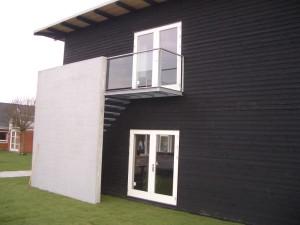 Modulbyggeriet har facader med sortmalet træ samt hvide døre og vinduer.